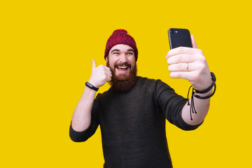 Close up portrait of a happy casual bearded man taking selfie and showing thumb up gesture