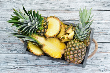 Pineapple in a wooden box. Tropical Fruits. Top view. Free copy space.