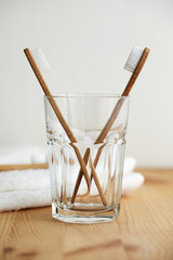 Two bamboo toothbrushes in a glass with a white towel on a wooden table