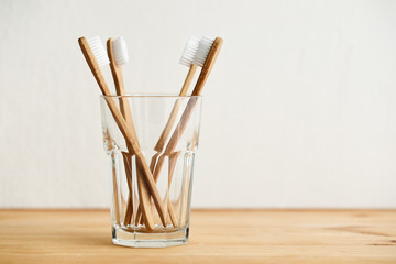 Four bamboo toothbrushes in a glass on a wooden table with copy space