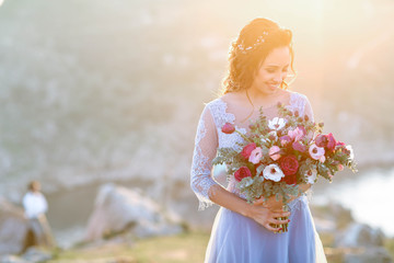 Beautiful bride in fashion wedding dress on natural background.The stunning young bride is incredibly happy. Wedding day. .A beautiful bride portrait at sea view