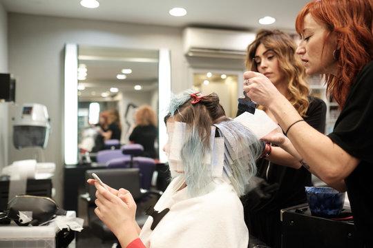 Una mujer recibe el tinte en una peluquería y se ven las manos de la peluquera