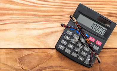 Calculator with glasses on wooden background. Top view. Space for text.