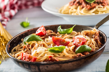 Italian pasta spaghetti bolognese in old pan with tomatoes parmesan cheese and basil