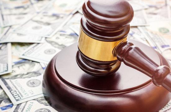 Judge's gavel on background of dollar bills.