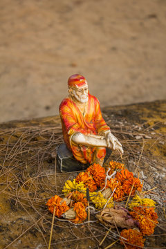 hinduism ancient statuette of the holy man Sai Baba with offerings on blurred background