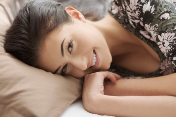 Young woman lying on a comfortable bed