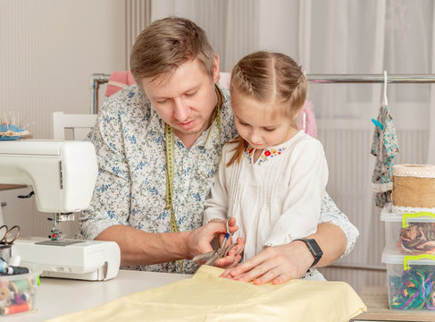 little girl and her dad in a sewing workshop