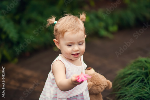 db37b3f87fd7 cute little girl smiling in a park close-up