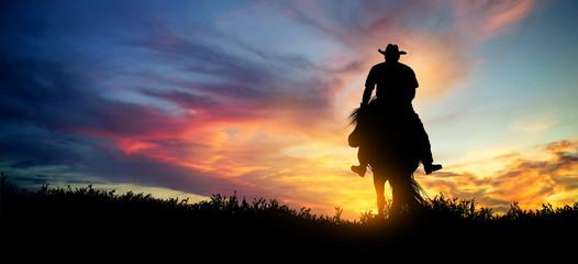 Obraz Cowboy on a horse at sunset - fototapety do salonu