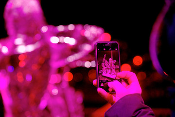 A man takes a picture with a mobile phone during the International Ice Sculpture Festival in Jelgava