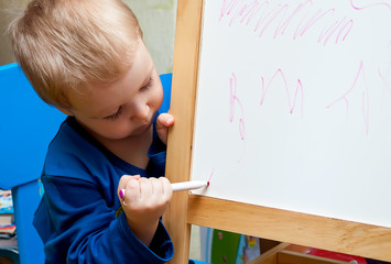 The little boy learns to draw on a white board.