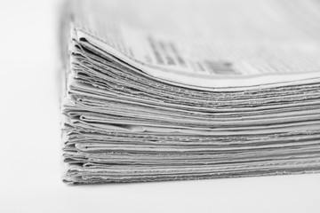 Pile of old newspapers on white background. Black and white photo.