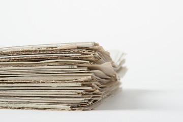 Stach of daily newspapers on a table. Pile of business papers on white background