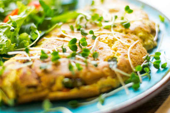 Vegan omelet made from chickpeas flour and soy milk with vegetables and green salad close-up. Concept of vegetarian and vegan food