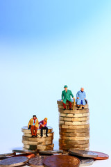 Conceptual diorama image of a miniture figure retired couple and young couple sat on a stack of pound coins