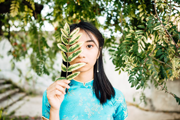 Portrait of beautiful Asian Chinese brunette in blue national dress outdoors, young Vietnamese woman in traditional clothes, the girl is resting in park