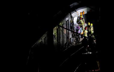 Rescue personnel inspect the site of a train crash near Manresa