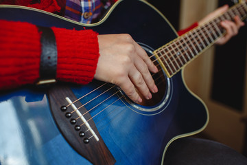 A girl plays the guitar in the studio. Musical instrument.