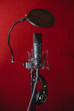 Microphone for recording music in the studio. Red background.