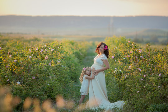 Happy pregnant woman with little daughter in a green tea rose garden