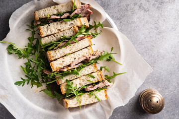 Overhead image of roast beef sandwich with rugula and mustard