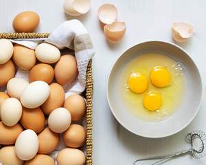 Brown and white eggs in a basket and raw eggs in a bowl.