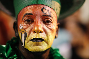 A member of a comparsa, an Uruguayan carnival group, poses for a picture before participating in the Llamadas parade