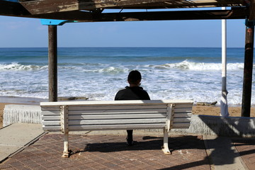 a bench stands in an open city park on the shores of the Mediterranean in Israel