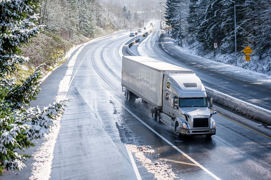 Big rig semi truck with semi trailer driving on winter snowy highway with wet melting snow surface