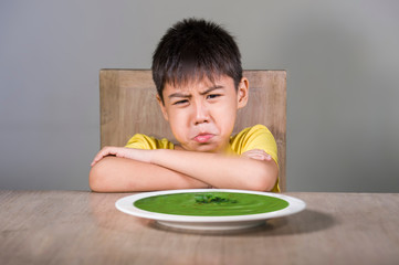 upset and disgusted Asian kid sitting on table refusing to eat spinach thick soup looking unhappy rejecting vegetarian food in child hate green vegetables and healthy nutrition