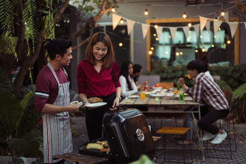 Couple are cooking for a group of friends to eat barbecue