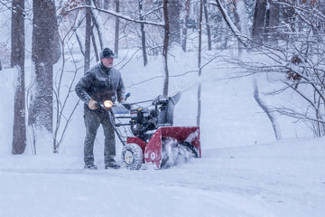An old white man is using snow blower to plow / blow snow