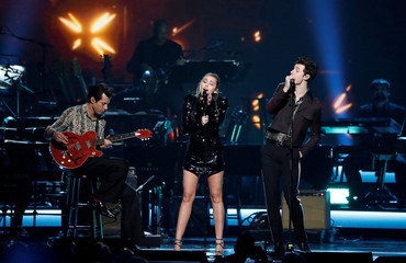 Miley Cyrus, Shawn Mendes and Mark Ronson perform during a gala event honoring Dolly Parton as the MusiCares person of the year in Los Angeles