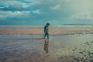 Little toddler running in the water on the beach