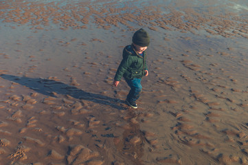 Little toddler standing on the beach in winter