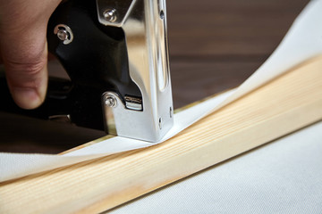 Canvas stretching on wood stretcher bar