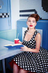 Retro (vintage) portrait of beautiful young woman sitting in cafe with book and beverage. Pin up style portrait of young woman in dress