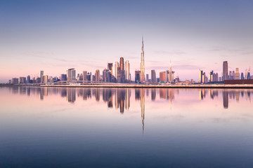 Beautiful colorful sunrise lighting up the skyline and the reflection of Dubai Downtown. Dubai, United Arab Emirates.