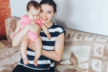 happy mother and baby girl in pink clothes playing at home