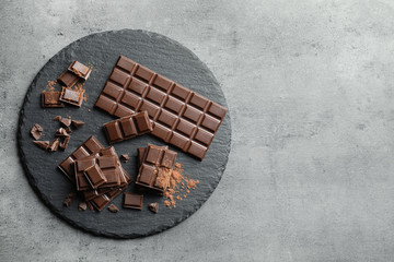 Fototapete - Slate plate with pieces of tasty chocolate on grey background, top view. Space for text