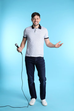 Handsome man in casual clothes posing with microphone on color background