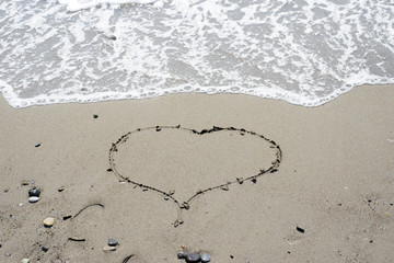 drawn on sand heart on the background of the sea waves