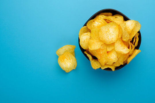 A photo of a bowl of potato chips with potatoes, shot from above on a blue texture with a place for text