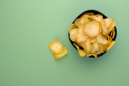 Potato chips in bowl on a wooden background, top view. Salty crisps scattered on a green background