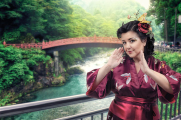 Caucasian woman in red kimono poses in front of the arched Japanese bridge