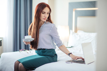 Long-haired female caucasian lawyer doing some work using notebook, while sitting on bed in a hotel and drinking coffee.