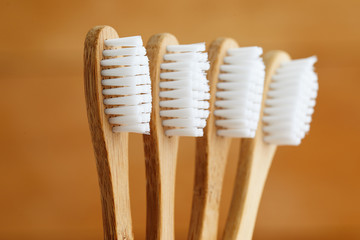 Close up of bamboo toothbrushes on brown background