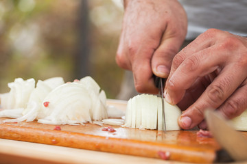 White onion slicing. Cook hands with knife