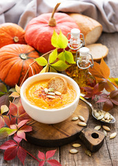 Bowl of pumpkin soup on rustic wooden background